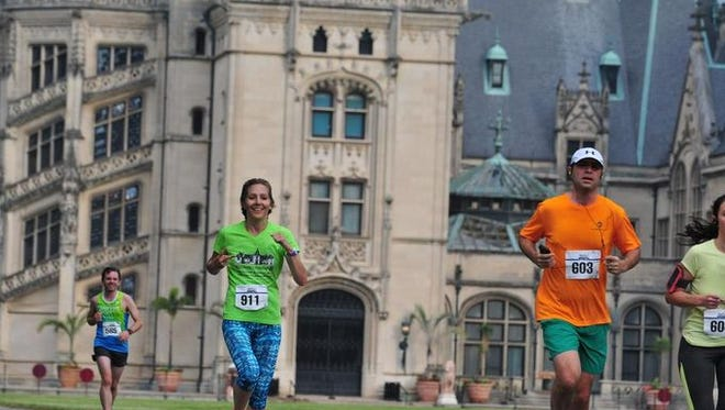 Runners pass the iconic Biltmore House Sunday morning during the 18th annual Biltmore/Kiwanis Classic 15K/5K race on the Biltmore Estsate.