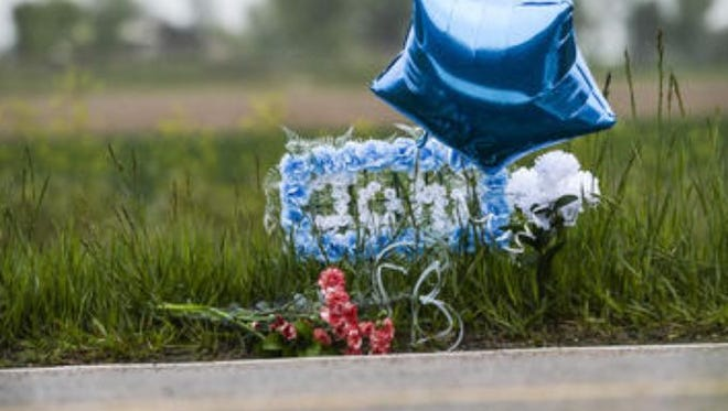"A memorial sits for John Jacoby on a rainy Tuesday afternoon, May 19, 2015, on County Road 15, in Windsor, CO. Jacoby was fatally shot on County Road 15 while riding his bicycle Monday morning. ""He was always volunteering for everything,"" said Rogakis, who used to work with Jacoby. ""He was a wonderful man."""