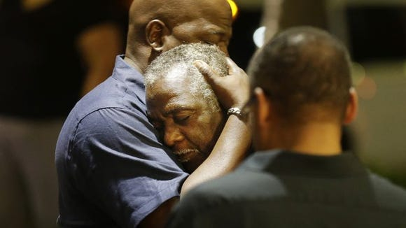 Worshipers embrace following a group prayer across the street from the scene of a shooting that left nine dead in Charleston.