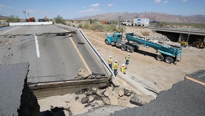 Caltrans workers on Tuesday, July 21, assess the damage to the Tex Wash bridge which shut down Interstate 10 between Coachella and Blythe in California.