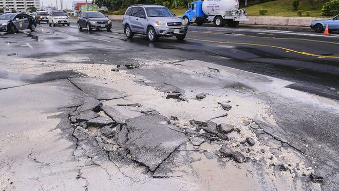 Motorists drive through a portion of Marine Corps Drive riddled with broken or rolling sections of asphalt on Monday, July 20.