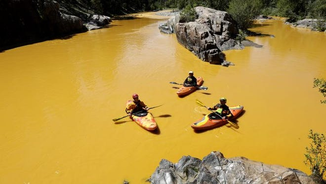 People kayak in the Animas River near Durango, Colo., Aug. 6, 2015, in water colored from a mine waste spill. The U.S. Environmental Protection Agency said that a cleanup team was working with heavy equipment Wednesday to secure an entrance to the Gold King Mine. Workers instead released an estimated 1 million gallons of mine waste into Cement Creek, which flows into the Animas River.