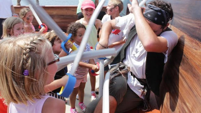 Children aboard the Good Fortune attack pirate and crew member Logan Rausch with their foam swords.