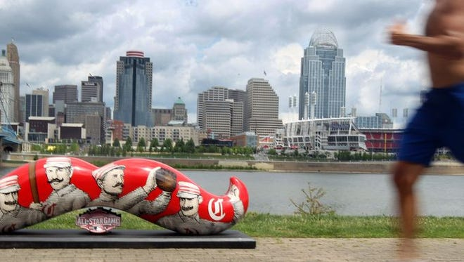 Dick Stewart, of Union, runs along Riverside Drive, Covington, past one of 10 All-Star Game Mustache Statues that have been placed around the area.