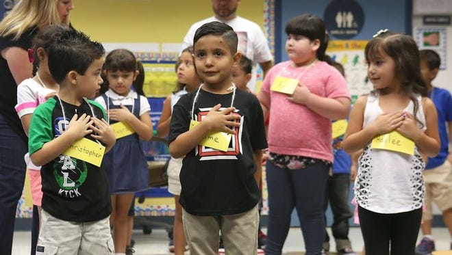 Kindergarteners at John Adams Elementary School learn how to say the Pledge of Allegiance on the first day of School Thursday.