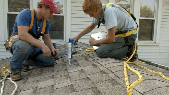Workers prepare to install solar panels on a home in