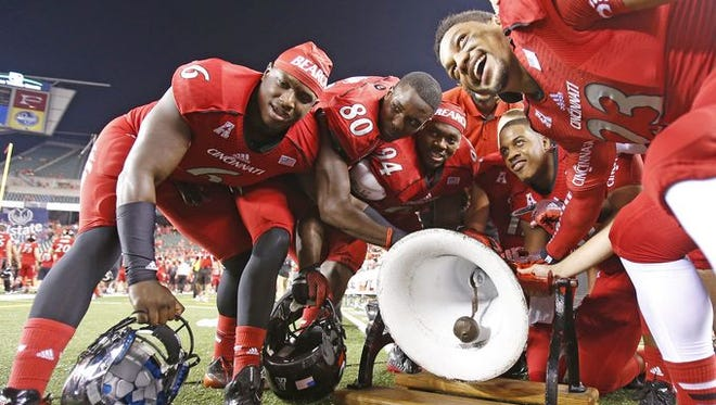UC players ring the Victory Bell after their 31-24 win over Miami in 2014.