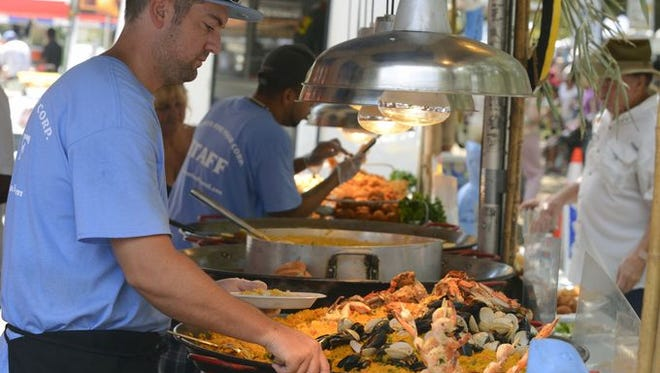 Justin Gutierrez of Captain Stevie's World's Best Seafood, serves up a helping Saturday morning during the Pensacola Seafood Festival at Seville Square