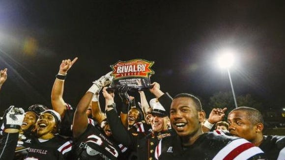 Asheville High football players celebrate with the