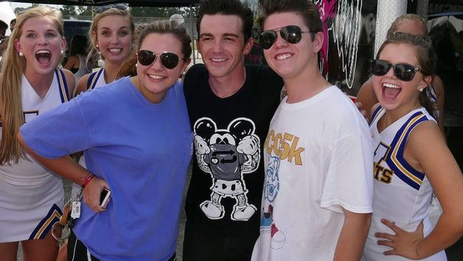 Drake Bell, center black shirt, has his picture taken with fans following his performance as part of the High School Nation Tour stop Wednesday afternoon at WHS.