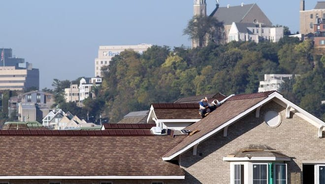 A roofer works on one of the homes in the Manhattan Harbour development, Dayton. The development will be the site of the Northern Kentucky Homebuilders Association HomeFest Oct. 3 through Oct. 18. Buildings at left are downtown; behind him and to the right is Mount Adams.