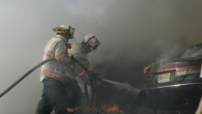 Firefighters from the Freehold Township Independent Fire Company extinguish a fire that destroyed six cars in the Freehold Raceway Mall parking, Wednesday afternoon, Oct. 21, 2015. A fire official said upwards of 20 firefighters and five pieces of firefighting equipment fought the blaze. Besides Freehold Independent Fire Company, the Freehold Fire Department, Freehold First Aid Squad and Freehold Township responded to the incident.