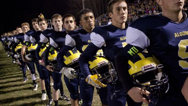 Algonac players stand at rest as the National Anthem is played during a football game Friday, November 6, 2015 at Algonac High School.