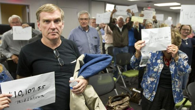 APP Taxed Out Town Hall attendees hold up their most recent property tax bill amounts.