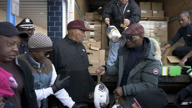"""Boxer Bernard 'The Executioner' Hopkins hands out turkeys at Price Rite in Camden on Thursday. Hopkins recalled his youth in Philadelphia's Raymond Rosen housing projects as a reason he came to Camden. """"I can relate to people in Camden because I grew up in North Philly, in the inner city, and even though I had a chance through my talent to travel around the world, I still kept conscious of where I came from,"""" he said."""