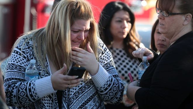 A woman cries at the scene of an active shooting on S. Waterman Ave in San Bernardino, CA
