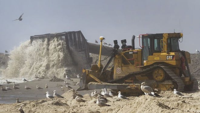 A bulldozer moves around reclaimed sand as it is pumped onto the beach in Ship Bottom on May 7, 2015.
