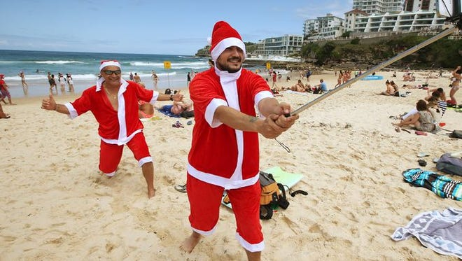 Father and son Santas Jean Claude Cathala, left, and Remy Cathala of France photograph themselves while celebrating Christmas Day on Bondi Beach in Sydney, Australia.