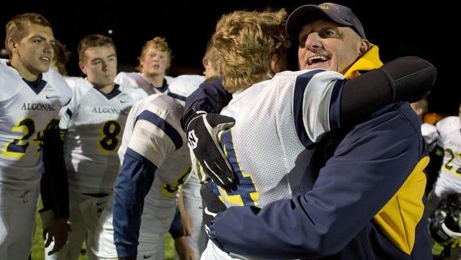 Algonac coach Scott Barnhart hugs players after beating Cros-Lex in a football game Friday, October 2, 2015 at Croswell-Lexington High School.