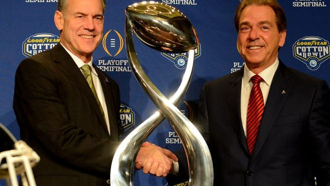 Nick Saban, right, and Mark Dantonio pose with the Cotton Bowl trophy before their final pregame press conference on Wednesday morning.