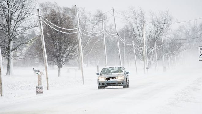 A light snow coats the road and nearby trees and power lines after snow fell Sunday.