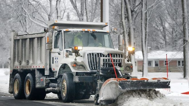 Crews clear roads from the ice and snow mix on Jan. 10, 2016.