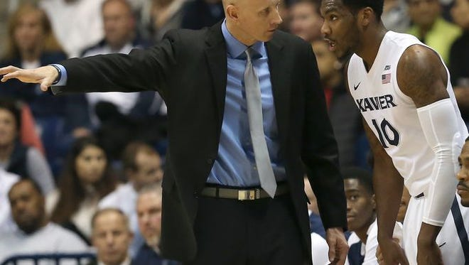 Chris Mack (left), Remy Abell and No. 7 Xavier return to action at 2 p.m. Saturday at Marquette. The Golden Eagles are 8-3 at home.