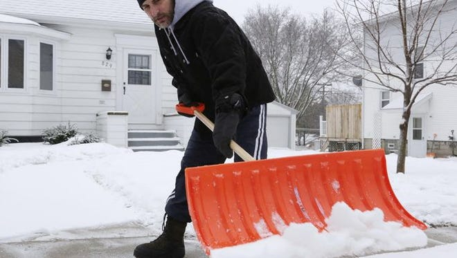 Brett Matz of Plymouth clears his sidewalk along Reed Street in Plymouth.
