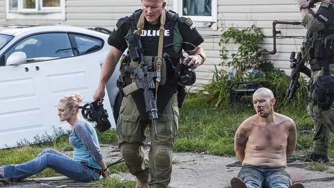 Jordan Kartholl/The Star Press A local police officer walks past handcuffed suspects at the scene of an August meth raid.