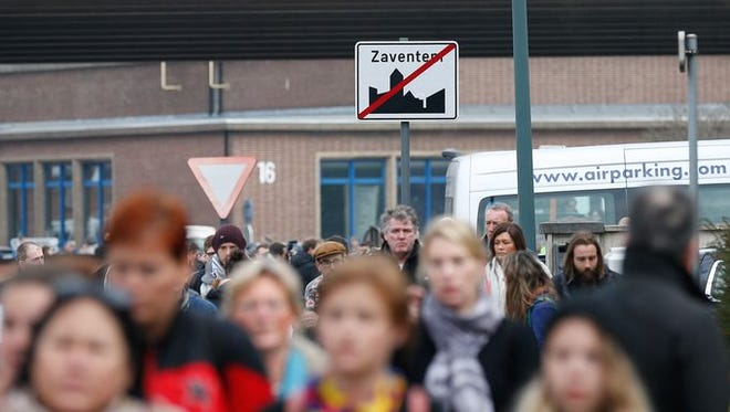 Passengers leave the airport area after explosions at Brussels Airport in Zaventem, Belgium.