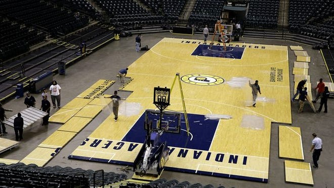 Members of the changeover crew remove the Indiana Pacers basketball court from the floor at Bankers Life Fieldhouse on March 31, 2016. The removal is in preparation for the NCAA Women's Final Four hosted at Bankers Life Fieldhouse.