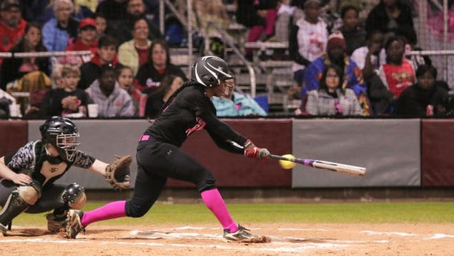 West Florida's Jibrasha Moore attacks a pitch vs. Tate earlier this season. All local softball district championship games have been postponed until Friday due to weather.