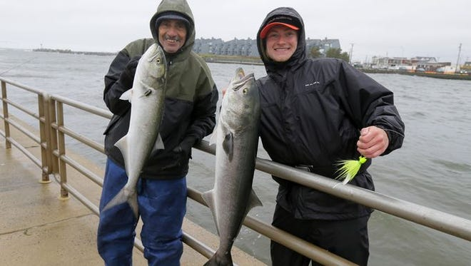 Gerard Buonanno of Florence and his grandson James Buonanno, Jr. of Burlington fish for bluefish in the rain at Manasquan Inlet on Friday, May 6.