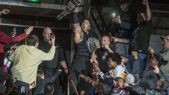 WWE world heavyweight champion Roman Reigns arrives through the Garrett Coliseum crowd Jan. 9.