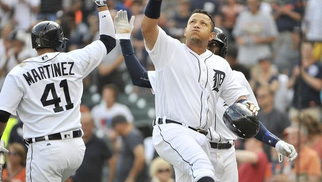 Tigers slugger Miguel Cabrera, right, is congratulated by Victor Martinez Monday.
