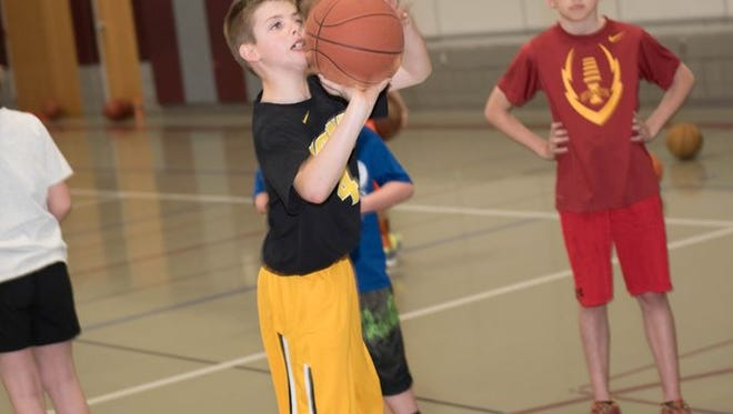 Bradley Olinger, 9, a fourth grader at Northwest Elementary, lines up for a freethrow at Ankeny Parks and Recreation's March Madness basketball event at Prairie Ridge Middle School on March 19.