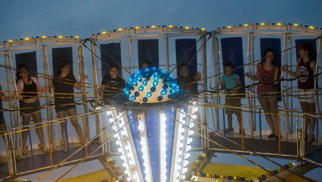 Fair-goers experience one of the spinning carnival rides at the Delone Catholic High School Carnival on June 15, 2016.