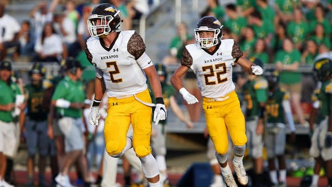 From left, Kickapoo football players Travis Vokolek (2) and Cole McCarville (22) celebrate a defensive stop at Parkview's JFK Stadium on Friday, Aug. 16, 2016. Kickapoo beat Parkview 55-26.
