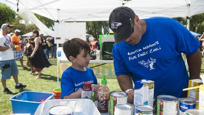Jeremy Levy, 9, and his father, Matthew Levy, both of Cockeysville, Md., consult on the chili-making process on Sept. 4, 2016.