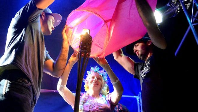 Event organizers demonstrate how to light a lantern for mass ascension at the first Lantern Festival in Fernley in 2014.