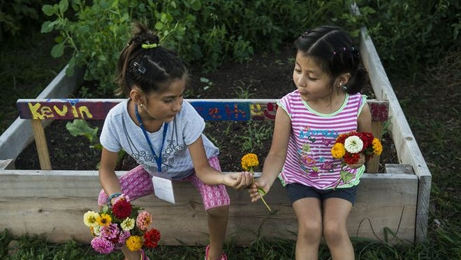 Two young gardeners share their collection of picked flowers as they rest on a garden plot at Painted Turtle Farm on Aug. 8, 2016.