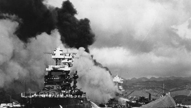 The hull of the capsized USS Oklahoma is seen at right as the battleship USS West Virginia, center, begins to sink after suffering heavy damage, while the USS Maryland, left, is still afloat in Pearl Harbor.