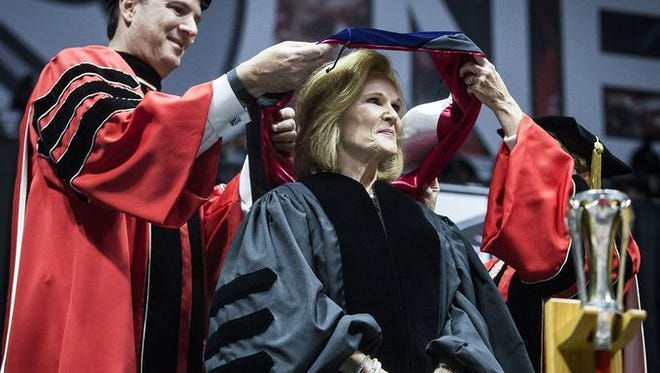 Rick Hall, chairman of the board, helps award an honorary degree to Indiana Higher Education Commissioner Teresa Lubbers at Ball State University's spring commencement.