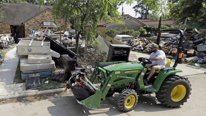 Justin Schultz uses a tractor to help remove debris from neighbors' homes destroyed by floodwaters in the aftermath of Hurricane Harvey on Sept. 3, 2017, in Spring, Texas.