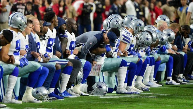 Dallas Cowboys take a knee prior to Monday's game with the Arizona Cardinals