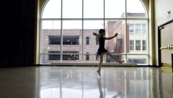 A dancer rehearses in the Appell Center for the Performing