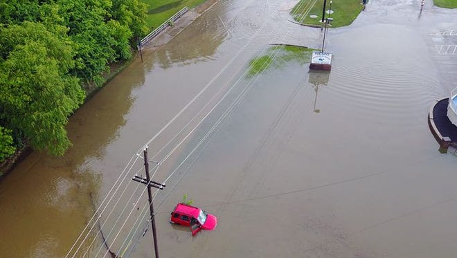 A car sits stranded window deep in flood waters along Industrial Highway in Springettsbury Township, Monday July 17, 2017. John A. Pavoncello