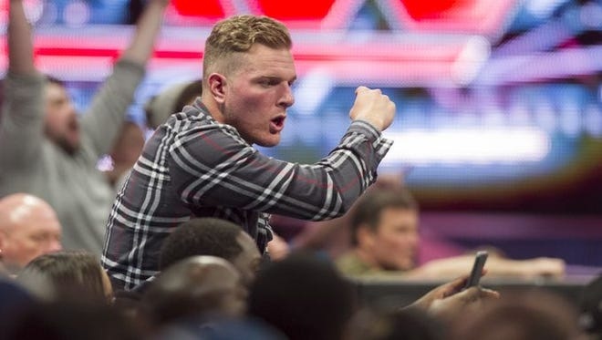 Indianapolis Colts punter Pat McAfee tries to encourage a wrestler to return to the ring to continue the fight after being thrown out by an opponent.
