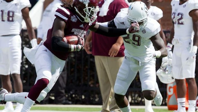 Mississippi State wide receiver De'Runnya Wilson stiff arms a defender against Texas A&M.