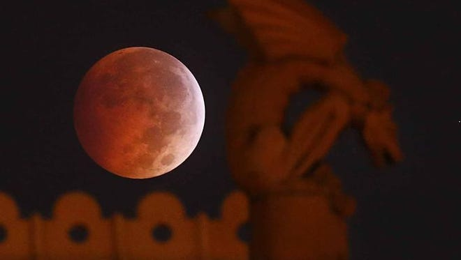 A so-called blood moon appears behind a gargoyle on the old Dallas County Courthouse during a lunar eclipse in Texas. Sunlight scattering off Earth's atmosphere causes the moon to appear orange or red. A partial lunar eclipse will happen Wednesday morning over southern lower Michigan.